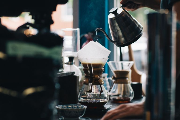 Barista pouring water over coffee using a Chemex